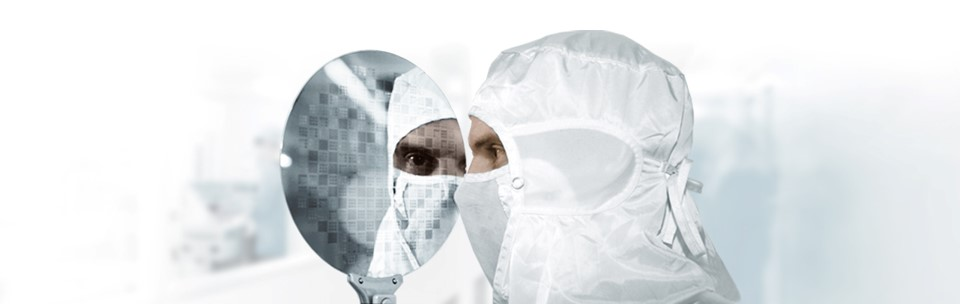 Person dressed in clean room suit holding a wafer.